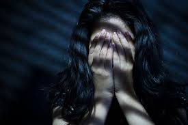 women sat in shadows with her hands over her eyes